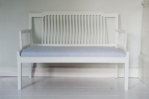 Liten vit soffa med klädd sits